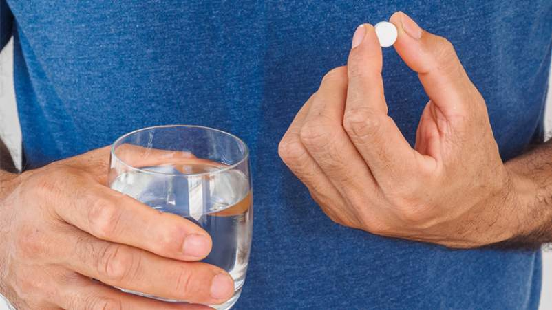 Man taking aspirin with a glass of water.
