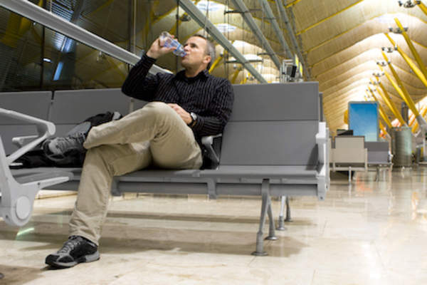 Man drinking water before early morning flight.
