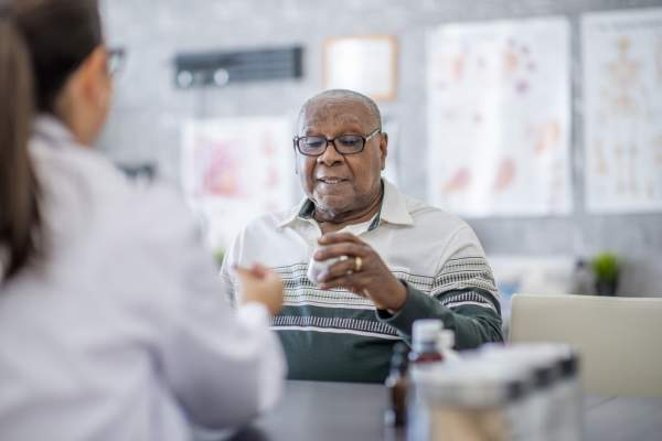 senior man with doctor looking at pill bottle