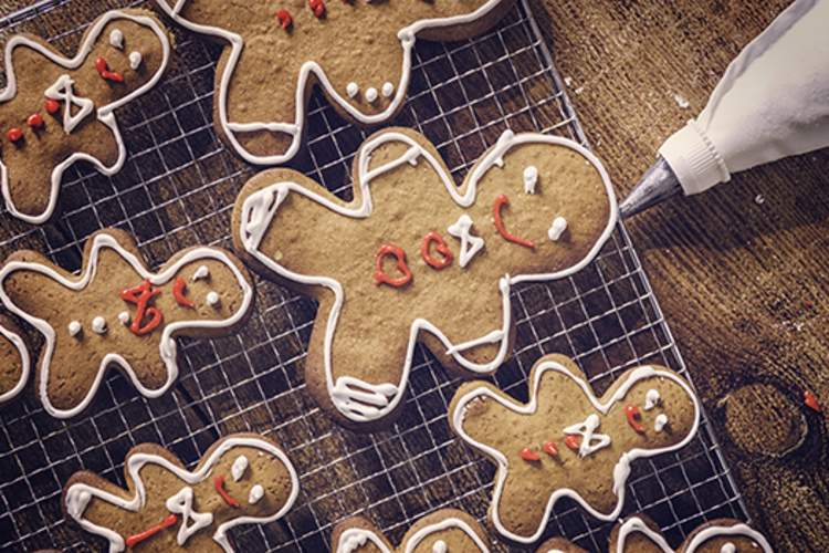 Decorating gingerbread men cookies with icing.
