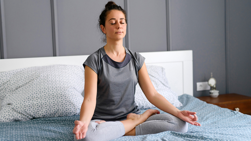 Woman meditating in bed.