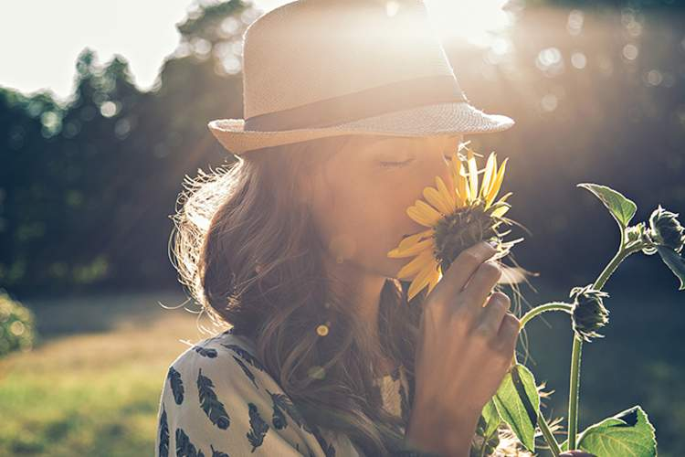Woman sniffing a sunflower.