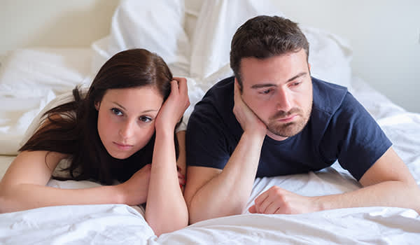 Young couple worried in bed.