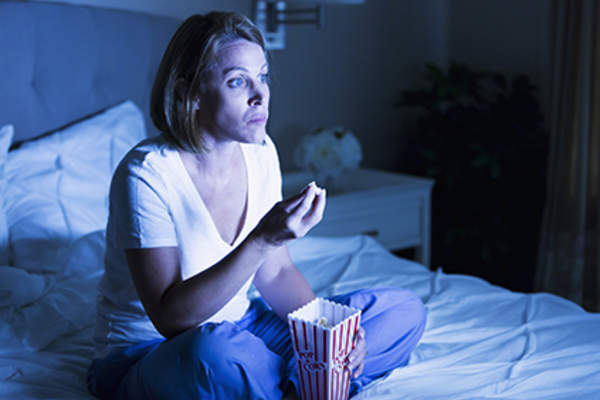 Woman staying up late and eating popcorn in bed.