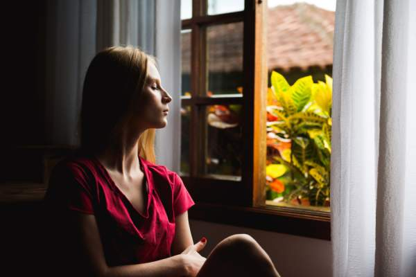 woman with eyes closed sitting next to window