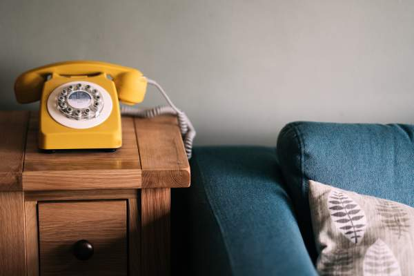 yellow phone on table next to blue couch