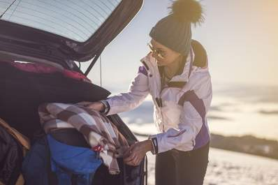 Woman packing her car for a winter vacation.