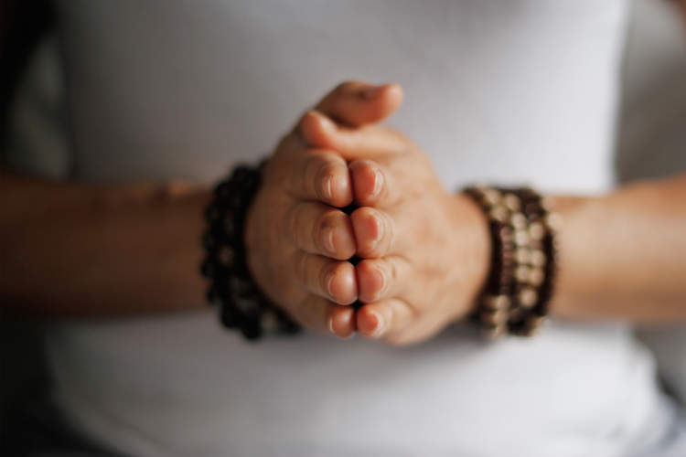 woman's hand practicing meditation prayer pose
