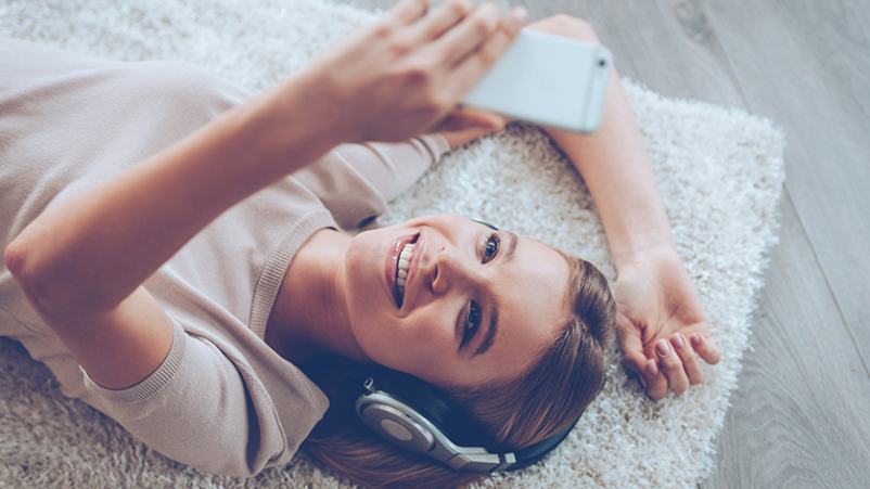 Woman lying down using her cell phone.