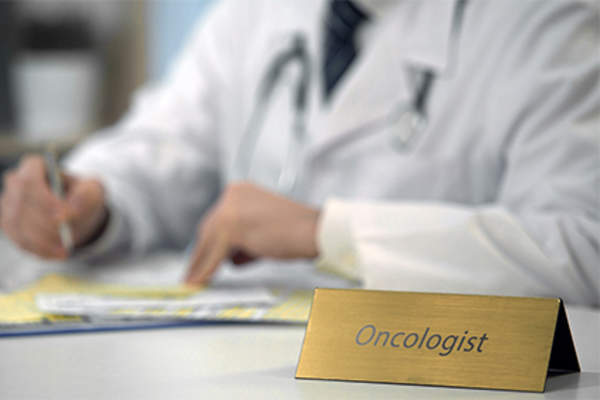 Oncologist working at desk.