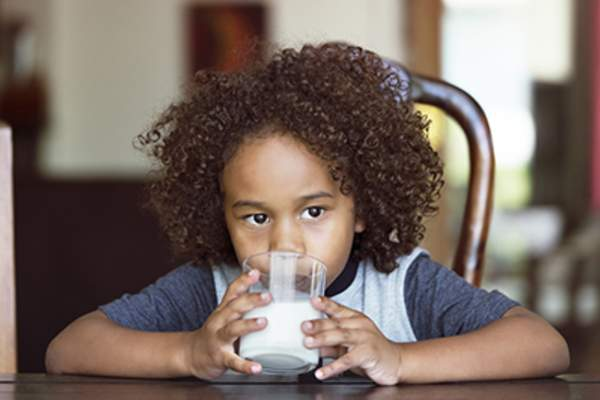 Child drinking a glass of milk.