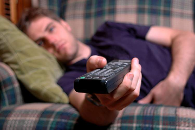 Man lying on couch with remote in hand binge watching television.