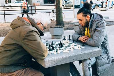 Young man and old man playing chess in the park