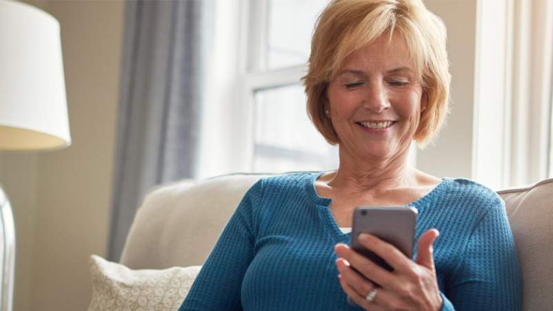 Middle aged woman using smartphone app.