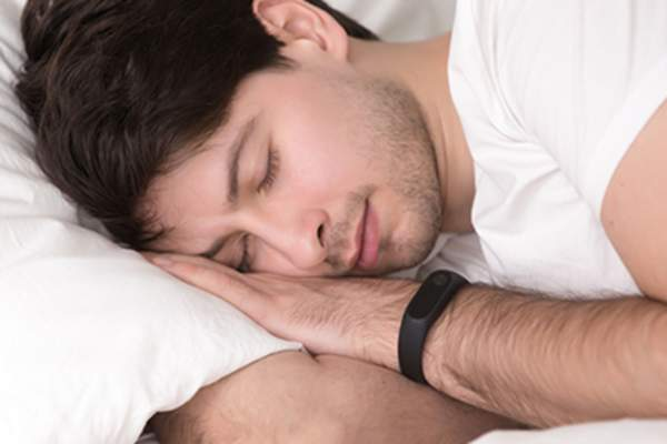 Man asleep in bed wearing smart wristband for sleep tracking.