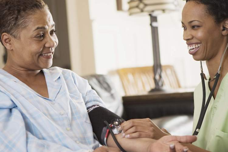 A nurse checks an elderly woman's blood pressure.