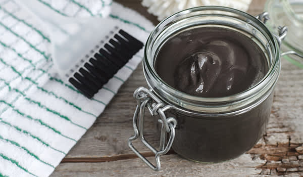 Black skin care product in a glass jar.