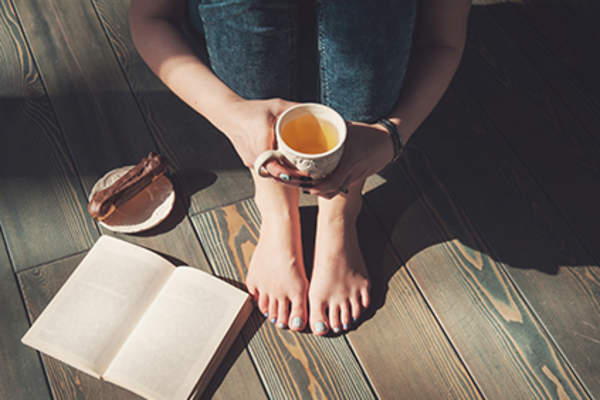 Woman sitting and drinking tea while reading a book.