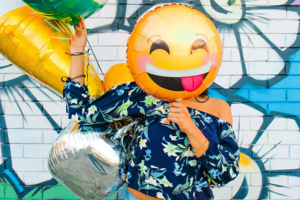 woman covering face with smiley balloon