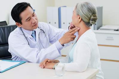 Doctor checking thyroid glands