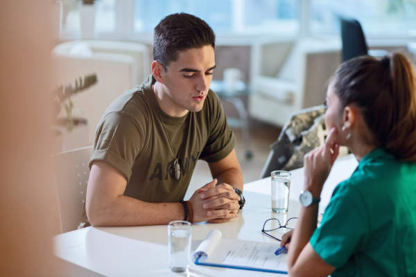 Young army soldier talking with doctor during his therapy
