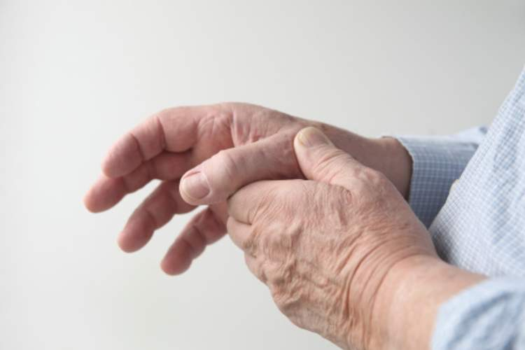 A man rubs his hand with rheumatoid arthritis joint pain.