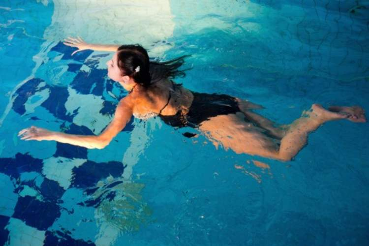 A woman swims in a pool to help her psoriatic arthritis.