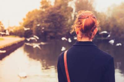 A woman looks at birds in a pond.