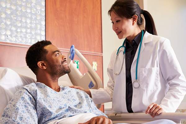 doctor talking to man in hospital bed image