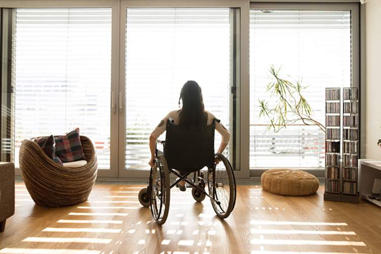 Woman in wheelchair in front of window.