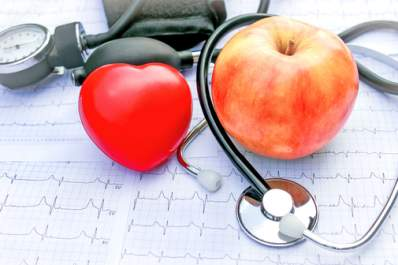 An apple, a heart, and a stethoscope on a table.