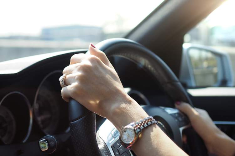 Woman's hands on steering wheel.