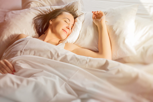 Woman looking relaxed in bed with white comforter.