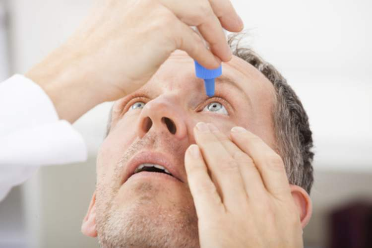 A man with dry eye putting eye drops in his eye.