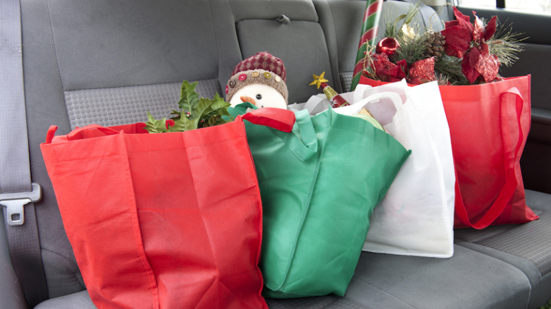 Holiday shopping bags loaded in backseat of car.