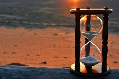 Hourglass on beach at sunset.
