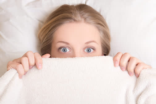 Woman with wide eyes peaking out from under covers.