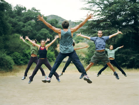 Fitness group does jumping jacks outside.