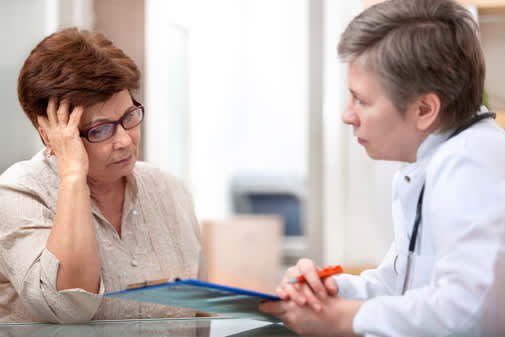 Woman in pain talking to her doctor.