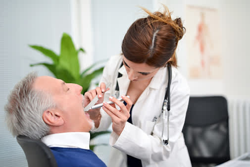 Doctor inspects a patient's tonsils.