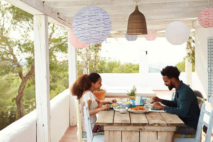 Man and woman share a meal at a table on an outdoor porch.