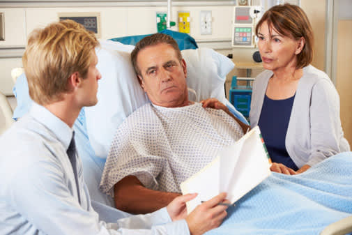 Doctor talking to man in hospital bed.