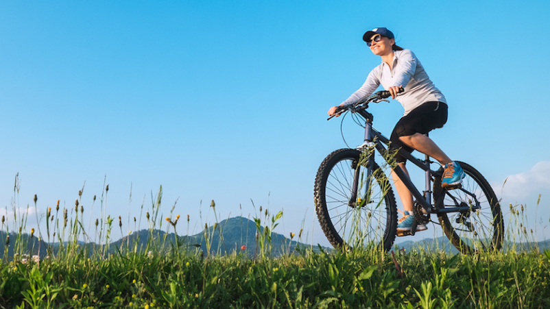 Woman riding bike outdoors.