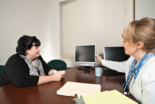 woman talking with doctor at desk