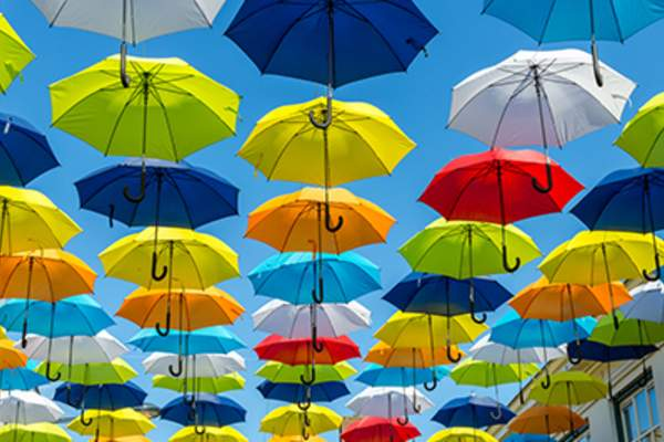 Brightly colored umbrellas against blue sky.