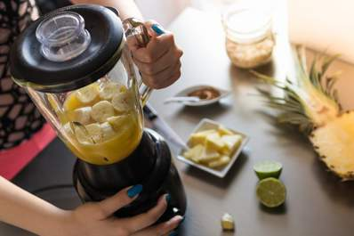 Woman making a smoothie in a blender.