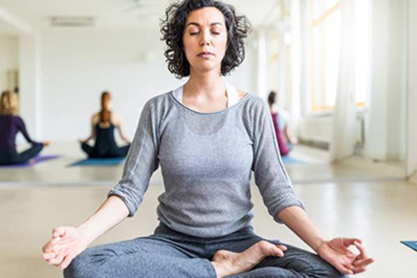 Woman meditating to minimize stress.