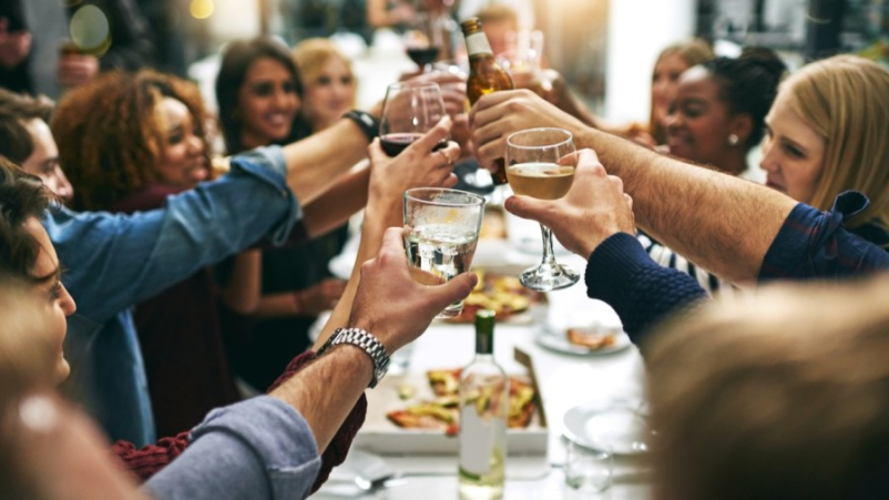 group of people cheers-ing at dinner party
