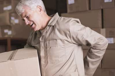 A man carrying a box grabs his lower back in pain.