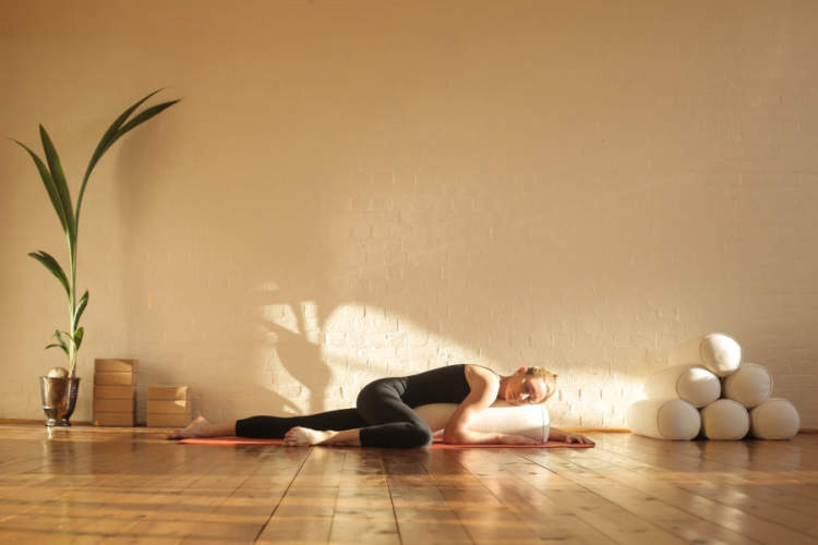 Woman practicing restorative yoga in a beautiful studio